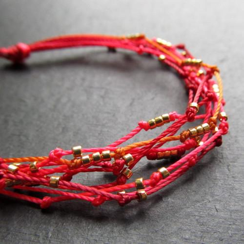 Náramek multi červené šňůrky zlaté korálky