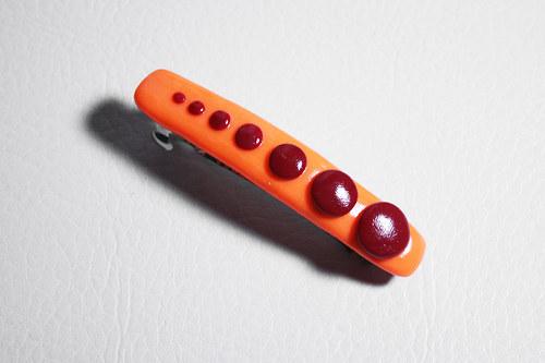 neonově oranžová spona s červenými tečkami