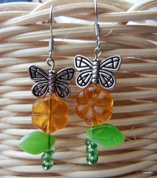 Motýlek na oranžové květině se stonkem