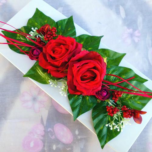 Červené růže na bílé lesklé misce