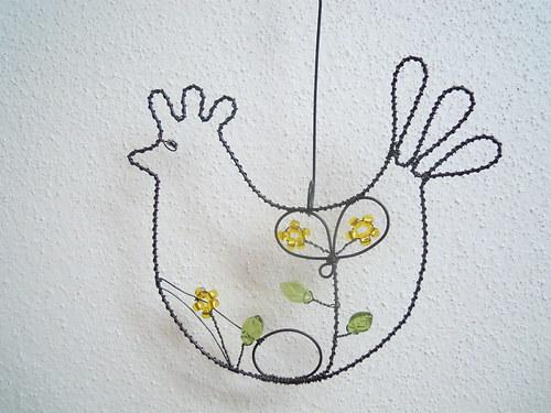 Snesla slípka vejce ve žlutém kvítí