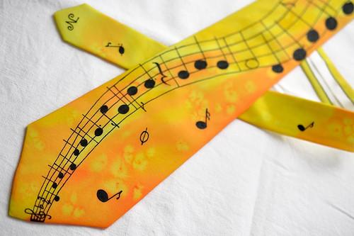 Žluto-oranž. kravata s černou notovou osnovou a no