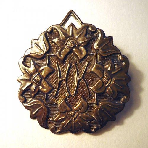 Zdobená kovová brož s monogramem