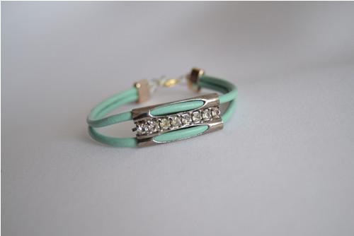 Kožený zeleno modrý náramek s kovovou ozdobou.