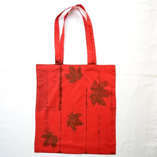 Červená plátěná taška s hnědou batikou a listy