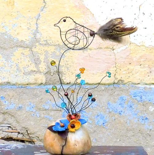 Ptáček s kytičkami na říčním kameni