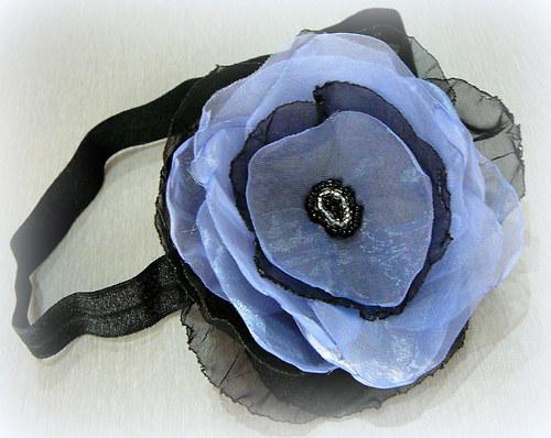 Čelenka s modročerným květem.