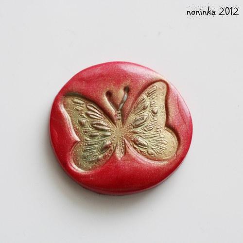 Červeno-zlatá placka s motýlem