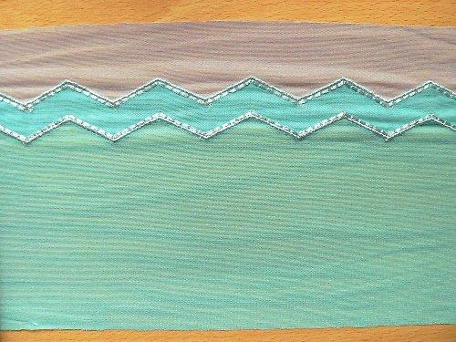 *Tyrkysový tylový lem s geometrickým vzorem.