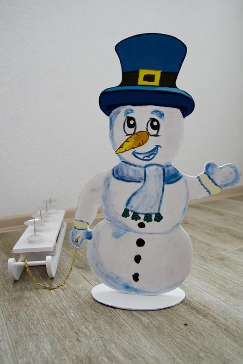 Dřevěný sněhulák se sáňky, jako adventní svícen.