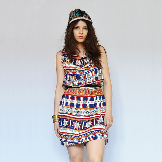 modelka má na sobě barevné krátke šaty s indiánskym vzorem